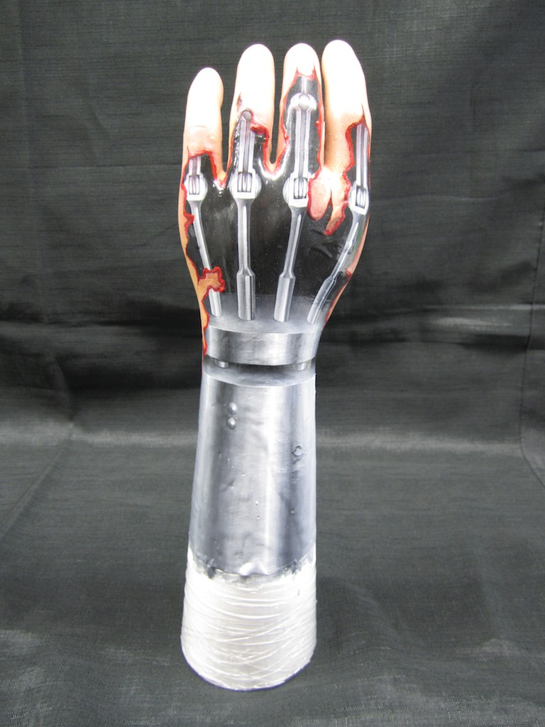 photo: Prosthetic hand tattoo painting by Hudson Valley NY artist Katrie Arena.  Metallic mechanical Terminator hand covered with ripped, bloody skin. Terminator Hand